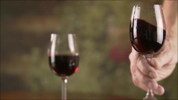 Mužské ruky míchání červené víno ve skle před ochutnávkou zpomaleně. Detailní záběr muž, který držel sklenici s červeným vínem