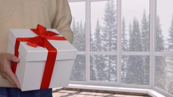 Muž představuje Dárková krabice s červenou stužkou na Vánoce. Oříznutý pohled člověka drží pro nový rok, sníh v lese za oknem
