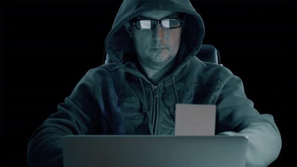 cc467d41854d Hacker en una sudadera con capucha y gafas que es sentado en la mesa de  noche y codificación. Hombre de hacker quita memo de pantalla portátil.  Vista frontal.