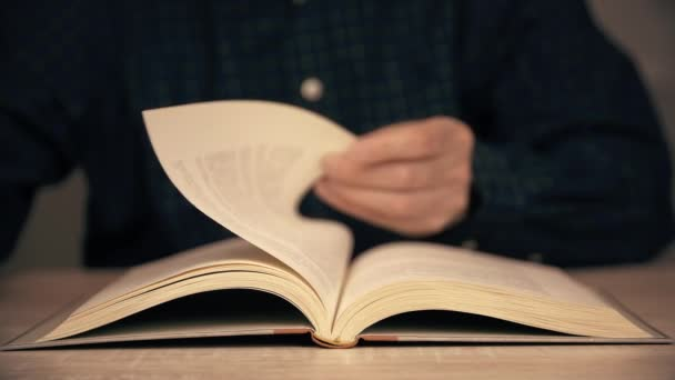 Male hand flipping book pages during reading close up. Man reading book and flipping pages