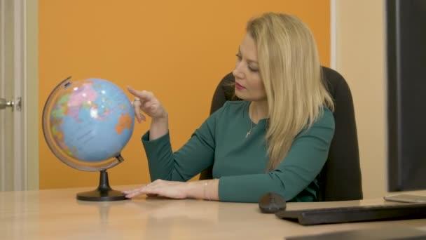 Krásná žena, otáčení zeměkoule mapu a při pohledu na země a kontinenty pro turistickou cestu v obchodní kanceláři. Obchodní žena hledá zeměkoule v cestovní kanceláři společnosti