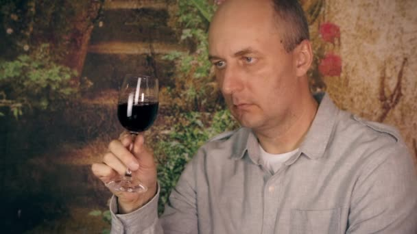 Adult man drinking red wine from glass and enjoy good taste close up. Portrait man sommelier tasting red wine from glass