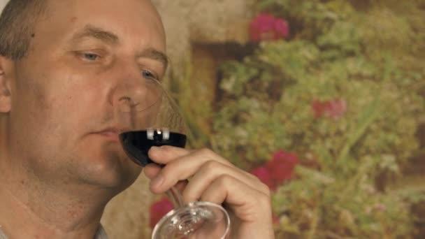 Portrét muže vinař při pohledu na červené víno ve skle a pití pro degustaci. Vážnou sommelier vína vonící a chutnající červené víno