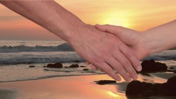 Amici che stringono la mano al tramonto sul mare sullo sfondo, vista ritagliata. Stretta di mano con due mani.