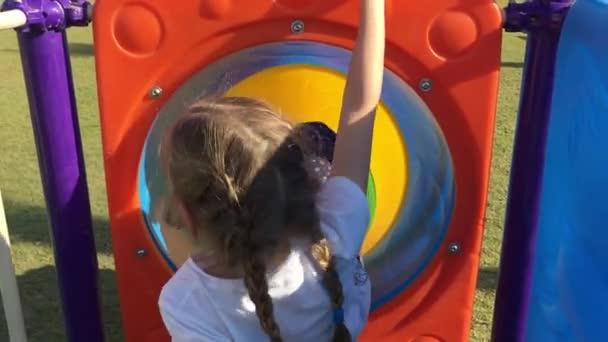 junges Mädchen, das in der bunten Tunnelrutsche sitzt, um auf dem Spielplatz hinunter zu reiten. Nahaufnahme spielerisches Mädchen reitet auf Kinderrutsche im Freizeitpark