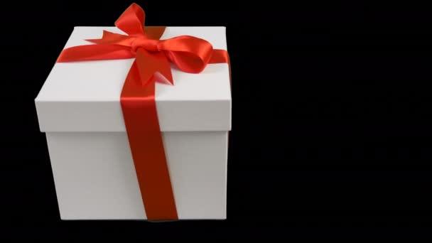 Bílá Dárková krabice s červenou stužkou luk stojí na černém pozadí.