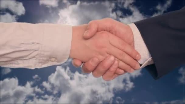 Uomo daffari che agitano le mani con affari con le due mani, cielo nuvoloso con il sole su priorità bassa. Vista potata della stretta di mano di affari dopo laffare