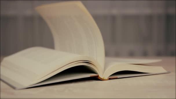 Nahaufnahme eines alten historischen Buches mit fallenden Papierseiten im Rückwärtsgang, Zeitlupe, Bildungskonzept