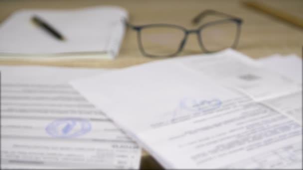 Professzionális üzleti dokumentumok és papírok, üvegek, toll és copybook a munkaasztalon, szelektív fókusz, nagyítás