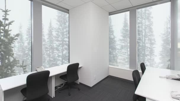 Prázdnou kancelář s židlemi a telefony na tabulkách, sníh v lese za oknem. Pozadí deska,