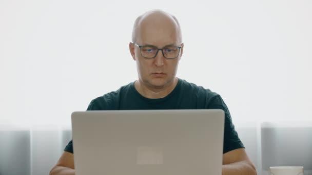 Obchodní muž čtení dat dokumentu na notebooku během práce v domácím studiu. Pohledný muž pracuje na notebooku sedí u stolu v domácí kanceláři