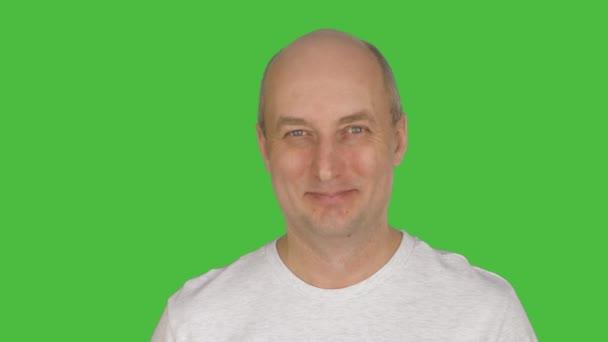 Portrait of bald mature man looking at camera, green studio background