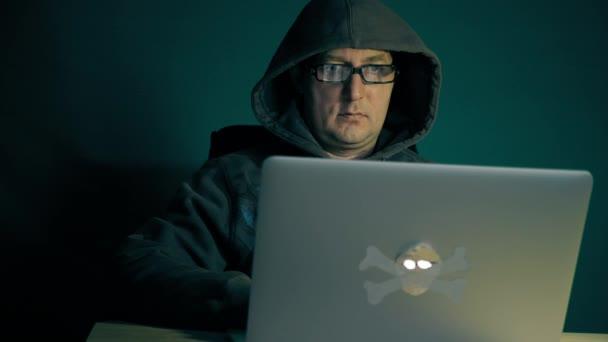 Dospělý Kavkazský hacker sedí u stolu s notebookem. Hacker v módní brýle kódování využít programy v Internetu. Bezva bezpečnostní systém. Sledování pohybu kamery. Pohled zepředu