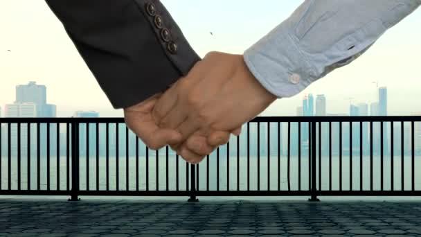 Obchodní dvojice ve formálním oblečení drží ruce. Řeka, přístaviště s zábradámi a centrem města s mrakodrapy na pozadí. Oříznuté zobrazení ruky v ruce