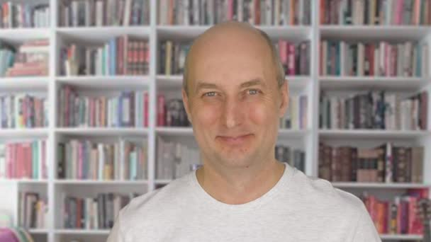 Portrait happy man smiling and looking into camera. Cheerful adult man n on bookcase background. Pleased middle aged man close up. Positive emotions concept