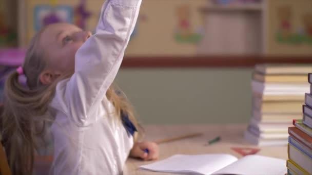 Vážných školačku myslet a dělat domácí úkoly na tabulky boční pohled. Happy školačku psaní nové myšlenky do školy notebook zblízka