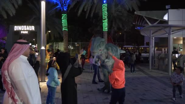 DUBAI, UAE - JANUARY 13TH, 2018: Arabian people afraid of animator in realistic dinosaur costume at night in Dino park, Dubai, United Arab Emirates
