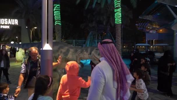 DUBAI, UAE - JANUARY 13TH, 2018: Happy children having fun with animator in realistic dinosaur costume at night in Dino park, Dubai, United Arab Emirates