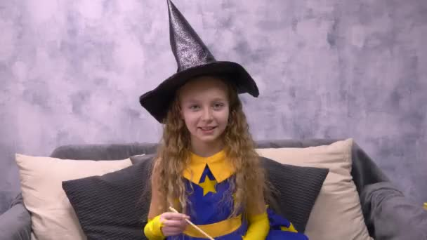 Stargazer wick warlock a magic mágus és varázsló kalapját show-hoz üres copyspace. Elölnézet aranyos tündér lány ül a kanapé fekete kalap helloween és a szép ruha csillagos pálca.