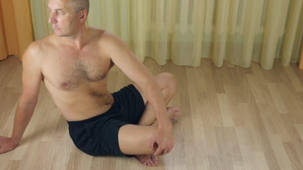 Erwachsener glatzköpfiger Mann, der auf dem Boden sitzt, in Lotus-Yoga-Pose meditiert, sich in der Stille konzentriert, Atem beobachtet, Geist, Seele und Körper entspannt. Ruhige Männer versuchen, Zen Harmonie zu erreichen.