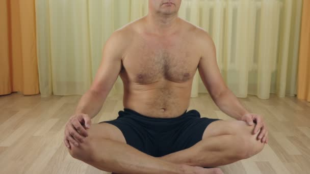 Adult Caucasian man sitting at floor in the room and doing yoga exercise. Muscular guy stretching his body at home. Training indoors. Close up locked down shot.