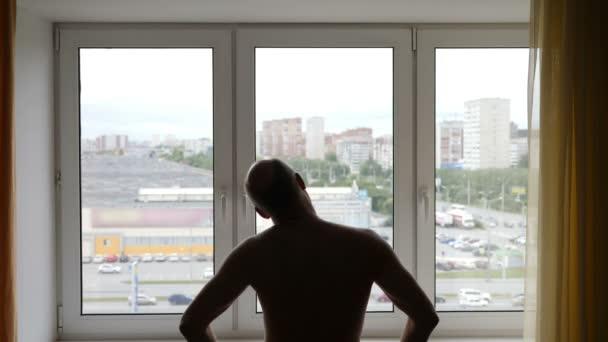 Silueta muže provádějícího cvičení uvnitř. Ranní cvičení před oknem. Gyu zahřívat krk do rána