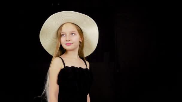 Mladá dívka v černých šatech a klobouk.