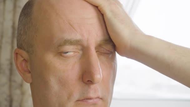 Dospělý Kavkazský běloch tře tahu holou hlavu, sám ručně na přirozené světlo podsvícení pozadí
