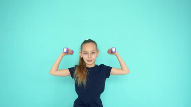 Young teenager girl lifting dumbbell at gym training on copyspace background