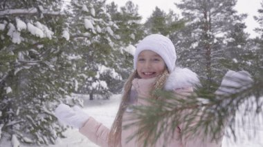 Smiling girl enjoying winter snowfall at snowy weather in forest slow motion