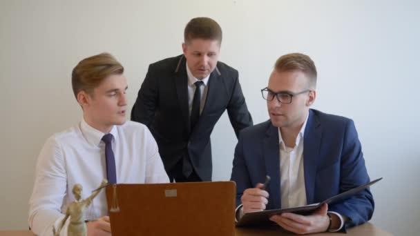 Tým právníků diskutovat podrobnosti nového obchodního projektu a hledáte notebook