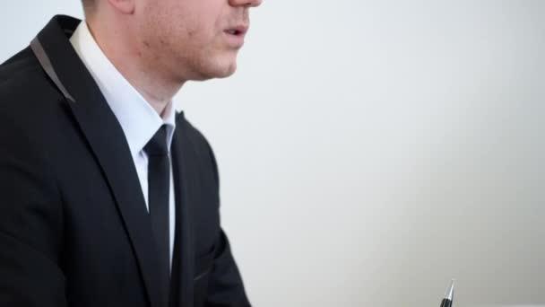 Portrét obchodní muž v černém suite drží v ruce pero a mluví na setkání