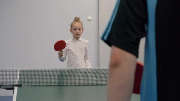 Mladá dívka hraje ping pong zpomalené. Sportovní dospívající dívka hraje ping pong