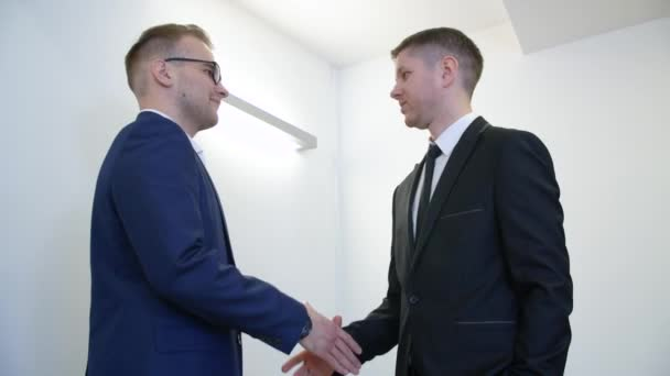 Two business partners shaking hands after successful deal in corporate office