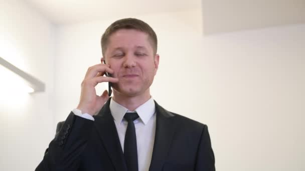 Portrait cheerful businessman smiling and talking by mobile phone in office