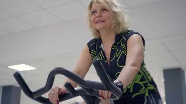 Mittleren Alter blonde Frau tut Übungen auf dem Heimtrainer. Sport-Konzept.