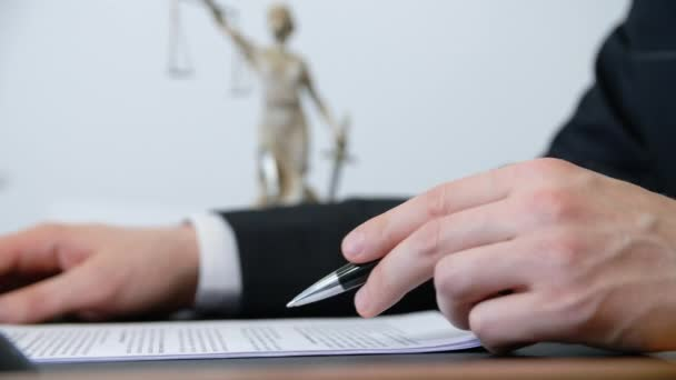 Closeup hand of lawyer signing contract with pen at work table in lawyer office