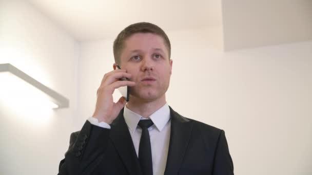 Jóképű üzletember öltöny és nyakkendő beszél a telefon hivatalban