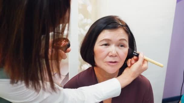 Malířka s kosmetickým kartáčem na make-up do dospělé ženy ve studiu