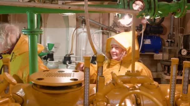 Women repairmen in yellow raincoats inspect engine room in boat in Norway.