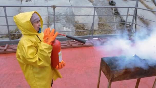 Samice hasičů v ochranném stejnokroji hasí v gril grilu plamen s hasicím přístroji. Žena hasičák, který při tréninku bojuje s ohněm. Tísňové služby.