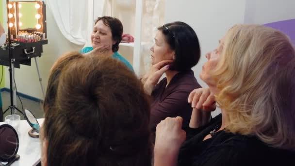 Seniorinnen lassen sich in der Gruppe selbst Gesicht massieren.