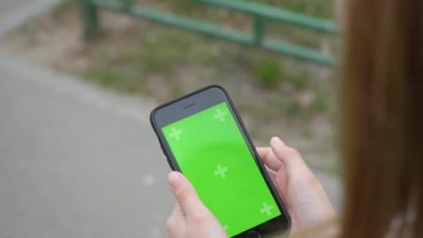 Dívčí ruka držící mobilní telefon se zelenou obrazovkou