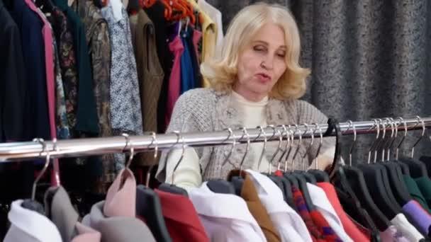 Starší blondýnka si vybírá oblečení v obchodě s oděvy. Koncepce nakupování.