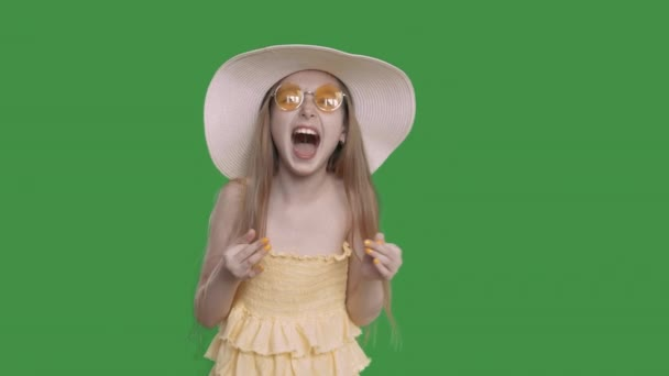 Happy young white caucasian girl with long hair yelow dress and summer hat laughing into camera
