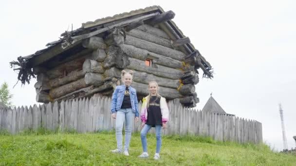 Két lány tinédzser állt a zöld gyep a forgó mese házat. Tinédzser lány pózol a fából készült ház a régi boszorkány mese faluban