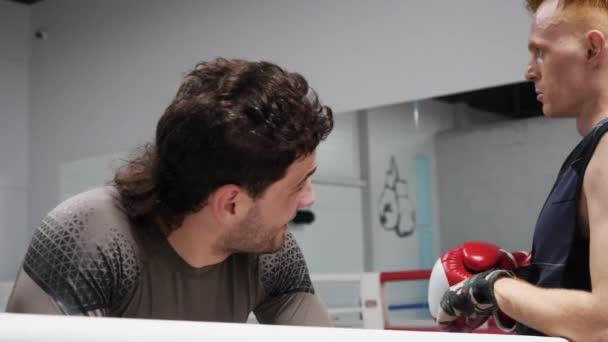 Müder Boxer ruht sich nach Kampf am Ringseil aus. Erschöpfter Boxer entspannt sich nach dem Training im Kampfclub. Sportlicher Lebensstil. Gesunder Lebensstil.