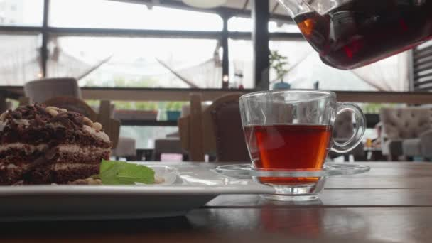 Pouring rich tea in glass cup from in transparent teapot on cafe table. Tea glass and chocolate pie on wooden table in summer cafe. Tea drinking in confectionery shop.