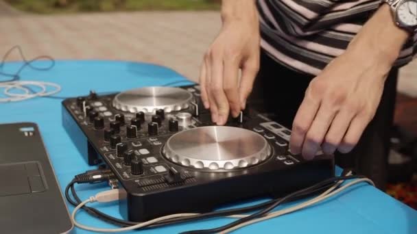 Close up DJ mixing music on sound console at outdoor party. Disc jockey playing music on controller panel. Mixing deck at summer party.