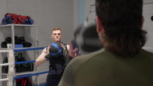 Cvičící sportovec hází medicínu na boxerský klub v bojovém klubu. Boxerci si házeli koule na trénink ve sportovním klubu. Cardio cvičení v tělocvičně.